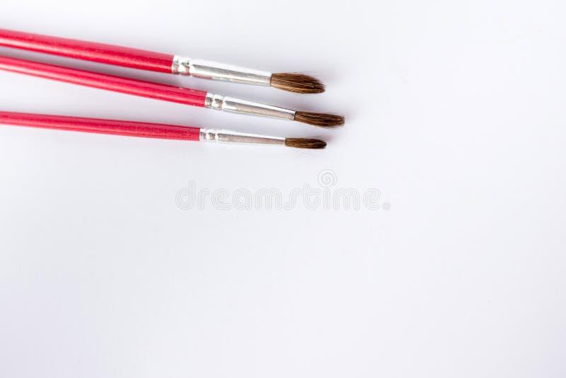 Chiuda su dei pennelli isolati su fondo bianco tavola per pittura testo fotografia stock