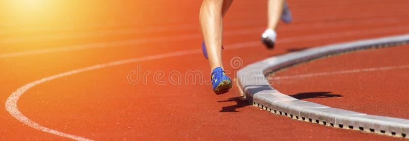 Chiuda su dei piedi dei corridori sul campo della pista Giorno pieno di sole fotografie stock libere da diritti