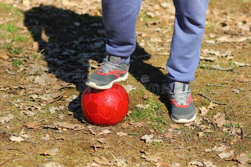 Chiuda su dei piedi del ` s dell'uomo che indossano i pantaloni e le scarpe da tennis di sport, con un piede su una palla rossa d immagini stock libere da diritti