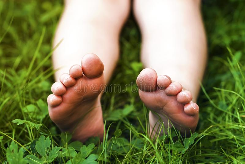Chiuda su dei piedi della bambina su erba verde fotografie stock libere da diritti