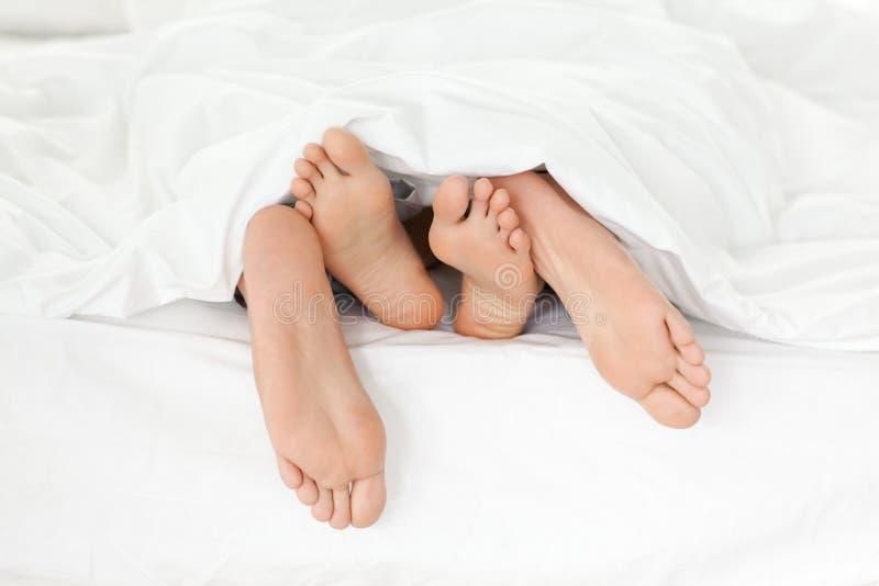 Chiuda in su dei piedi della coppia nella loro base fotografia stock libera da diritti