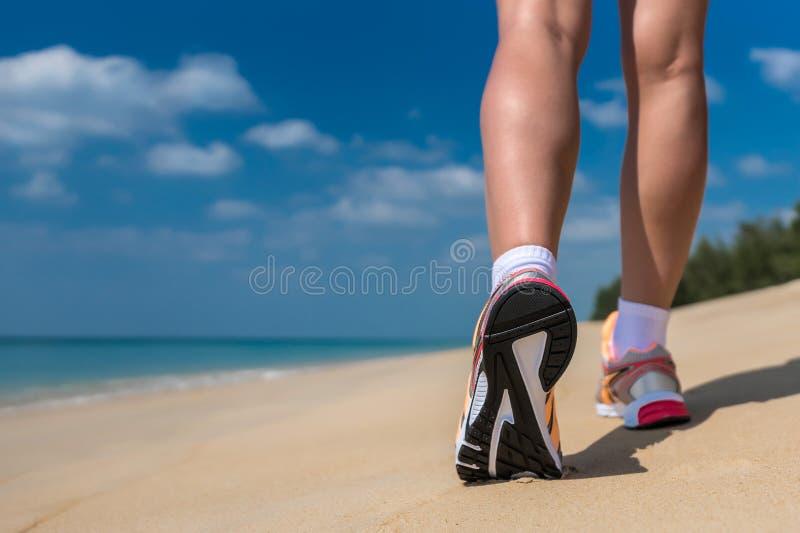 Chiuda su dei piedi di un funzionamento del corridore nell'addestramento della spiaggia per la maratona fotografia stock libera da diritti