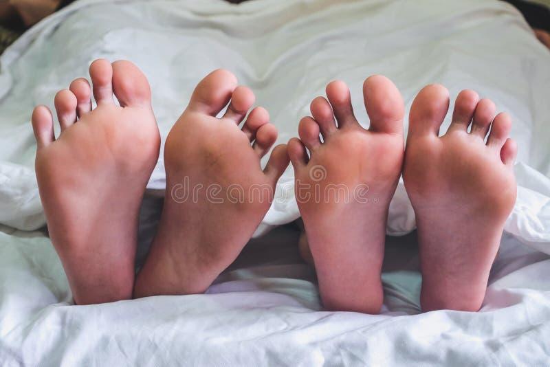 Chiuda su dei piedi maschii e femminili su un fare sesso delle coppie e del letto fotografia stock libera da diritti