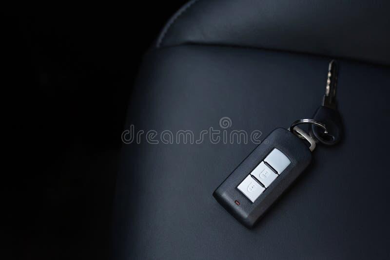 Chiuda su dei portachiavi a anello dell'automobile e di un sistema di allarme telecomandato o dimentichi le chiavi disposte sui s fotografia stock