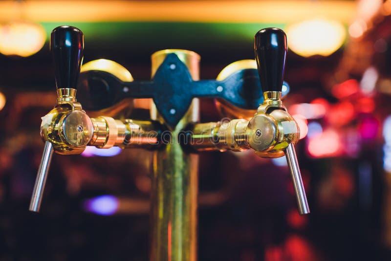 Chiuda su dei rubinetti della birra nella fila Attrezzatura metallica per le barre ed i mini brewerys Concetto di attrezzatura mo fotografia stock libera da diritti