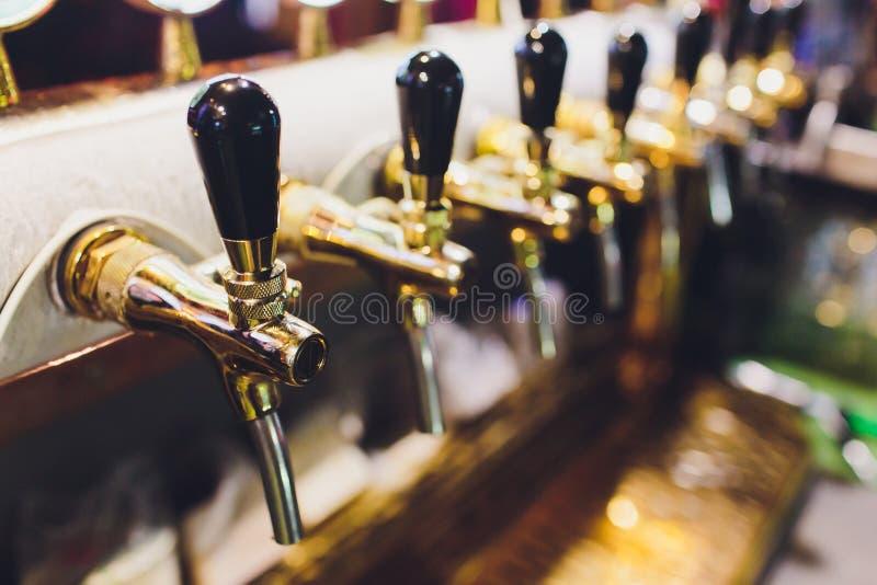 Chiuda su dei rubinetti della birra nella fila Attrezzatura metallica per le barre ed i mini brewerys Concetto di attrezzatura mo fotografie stock