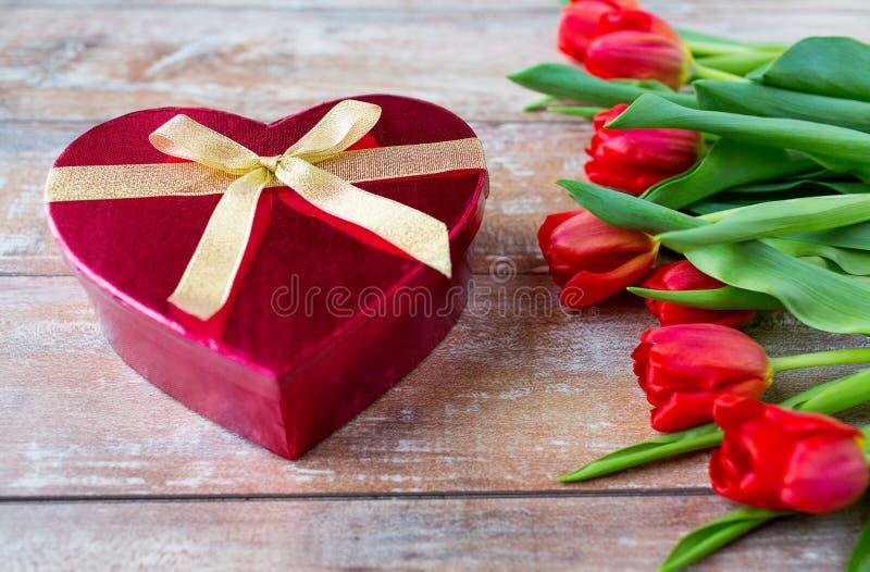 Chiuda su dei tulipani e del contenitore rossi di cioccolato fotografia stock