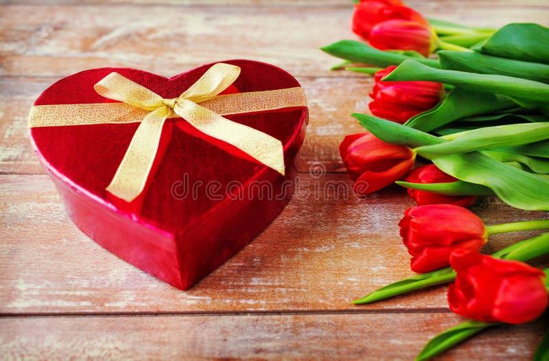 Chiuda su dei tulipani e del contenitore rossi di cioccolato immagini stock libere da diritti