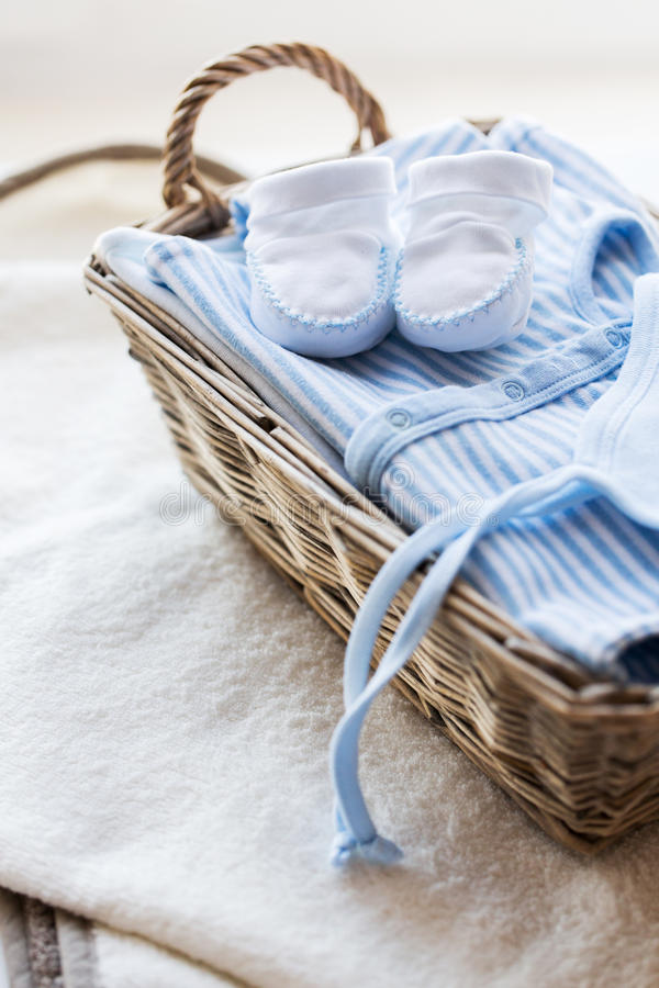 Chiuda su dei vestiti del bambino per la merce nel carrello neonata del ragazzo fotografie stock