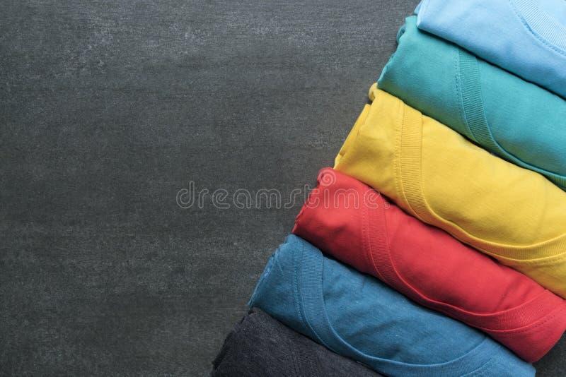 Chiuda su dei vestiti variopinti rotolati su fondo nero fotografia stock