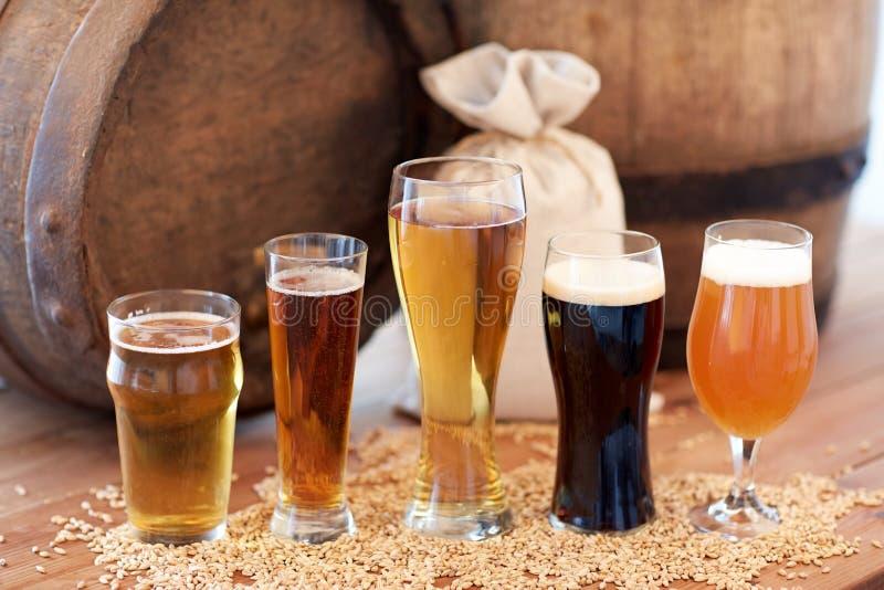 Chiuda su del barilotto, dei vetri e della borsa di birra con malto fotografia stock libera da diritti