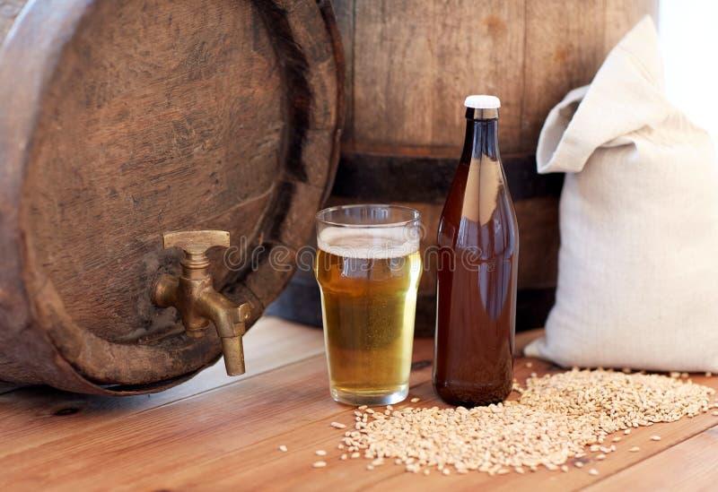 Chiuda su del barilotto di birra, del vetro, della bottiglia e del malto fotografia stock