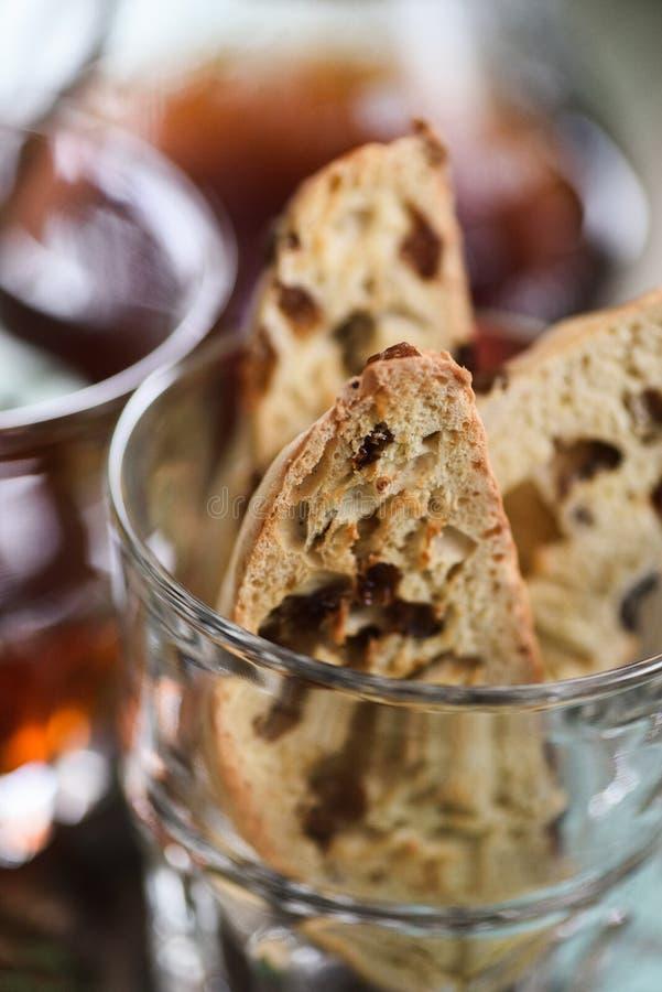 Chiuda su del biscotti o del cantucci italiano tradizionale casalingo con l'uva passa in vetro servito con caffè fotografia stock