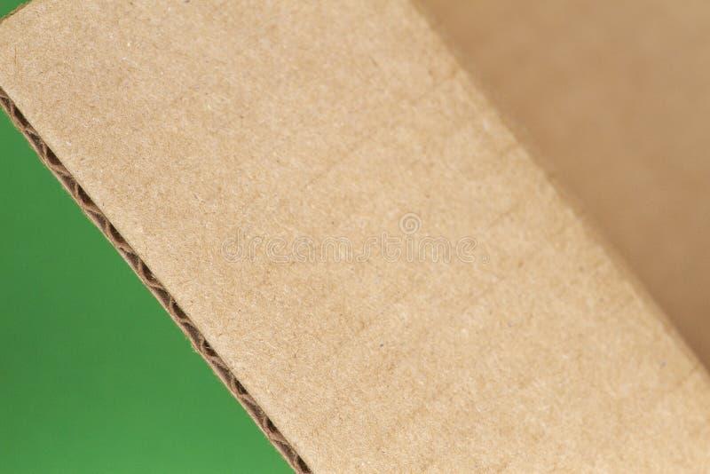 Chiuda su del bordo di scatola di cartone aperto su fondo verde immagini stock