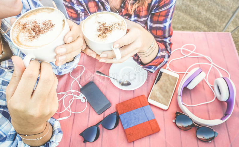 Chiuda su del caffè bevente del cappuccino delle coppie delle amiche immagine stock
