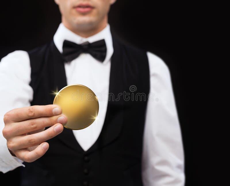 Chiuda su del commerciante del casinò che tiene la moneta dorata fotografia stock