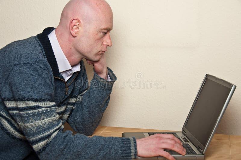 Chiuda in su del computer portatile usando maschio in portelli fotografia stock libera da diritti