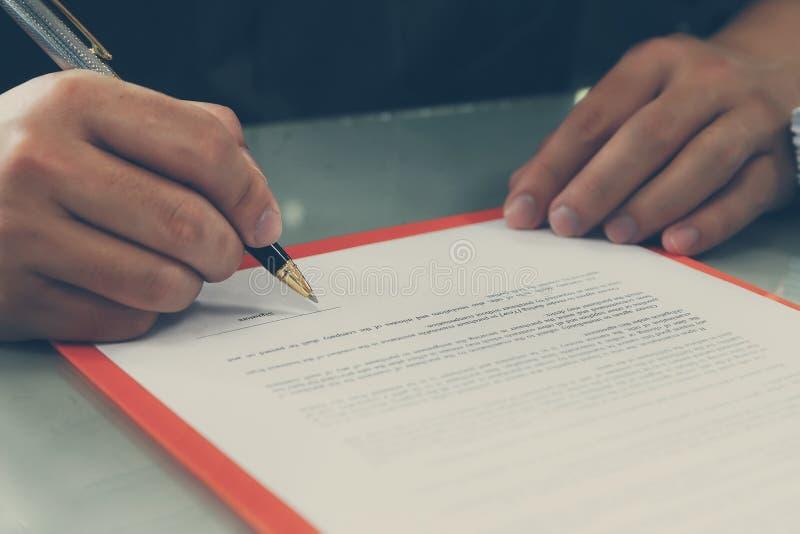 Chiuda su del contratto di firma dell'uomo di affari che fa un affare fotografie stock