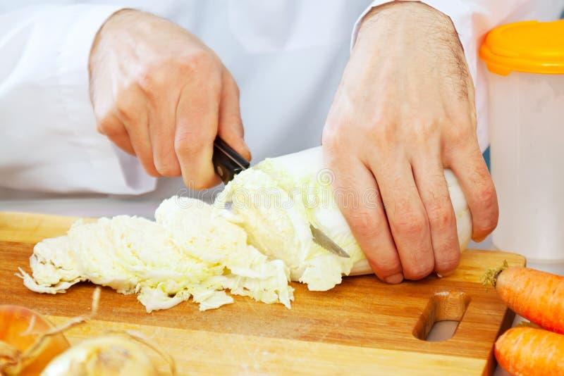 Chiuda su del cuoco unico che cucina le verdure fotografia stock libera da diritti