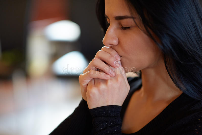 Chiuda su del dio pregante della donna infelice al funerale immagini stock