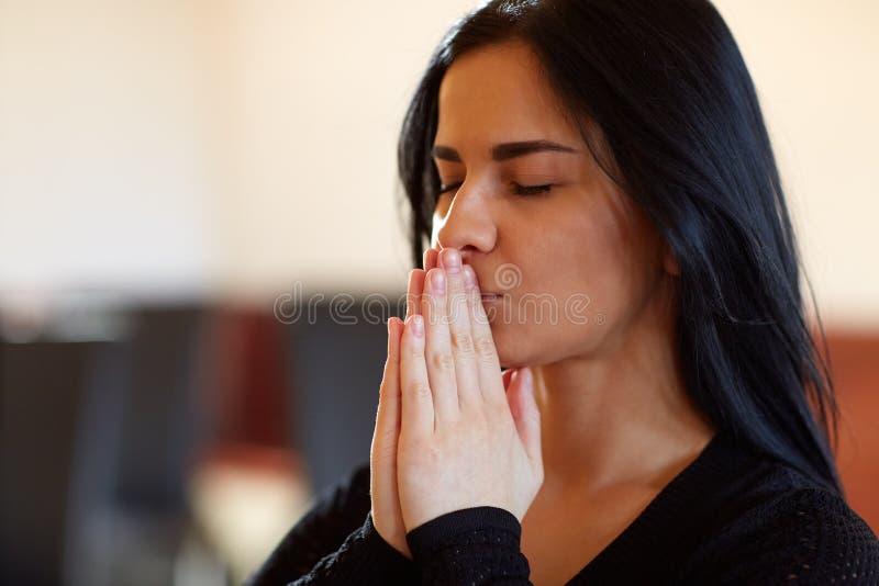 Chiuda su del dio pregante della donna infelice al funerale immagine stock