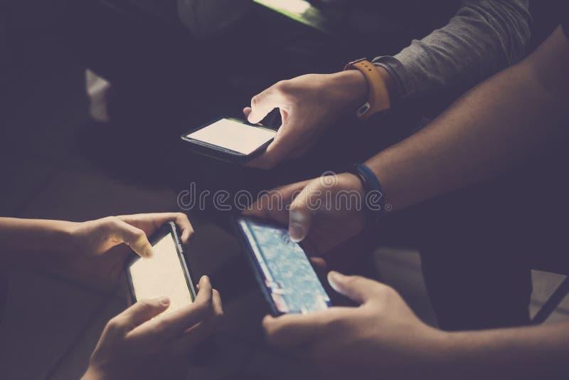 Chiuda su del dispositivo tre con i video giochi per i giovani amici caucasici che giocano insieme a casa come la tecnologia dedi fotografia stock libera da diritti