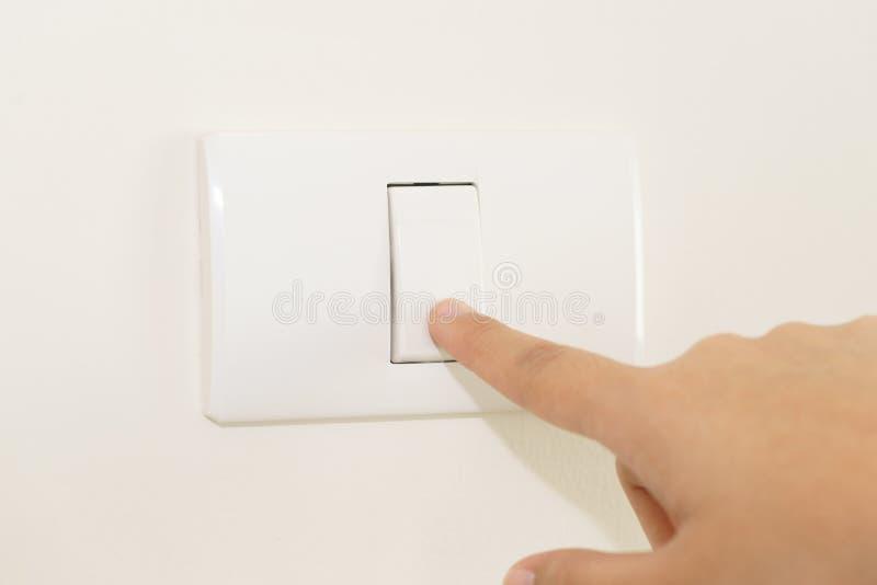 Chiuda su del dito che spegne sull'interruttore della luce sulla parete fotografia stock libera da diritti