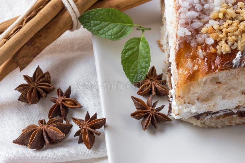 Chiuda su del dolce a sezione circolare con lo zucchero a velo, la crema, la menta, cinn fotografie stock