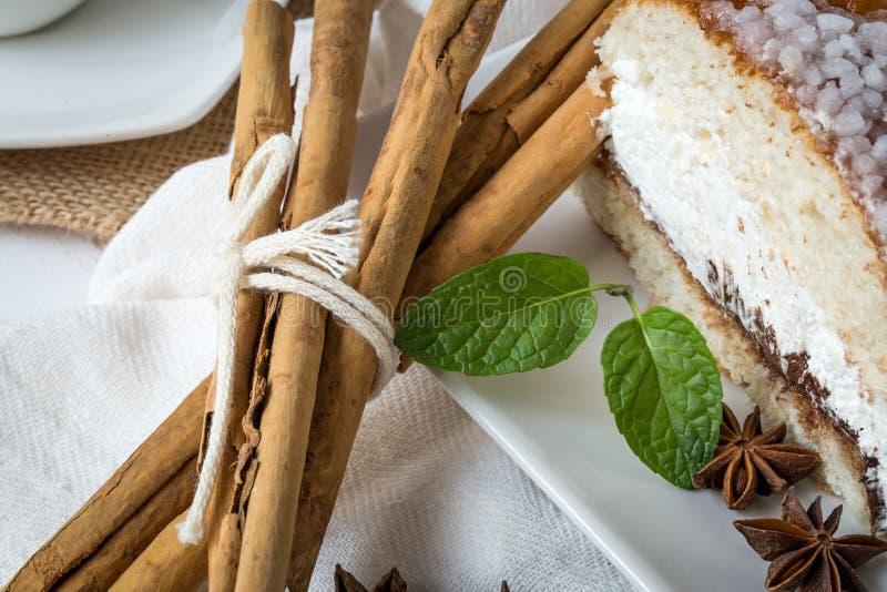 Chiuda su del dolce a sezione circolare con lo zucchero a velo, la crema, la menta, cinn immagine stock