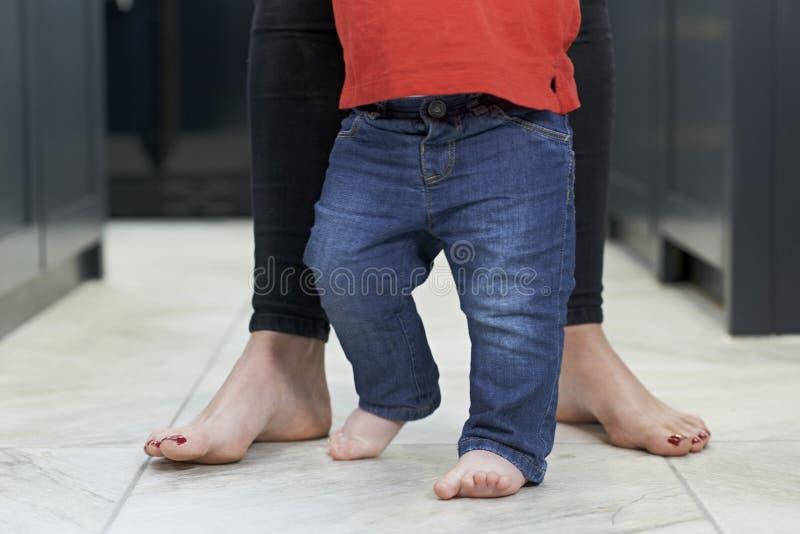 Chiuda su del figlio d'aiuto del bambino della madre per camminare in cucina fotografia stock libera da diritti
