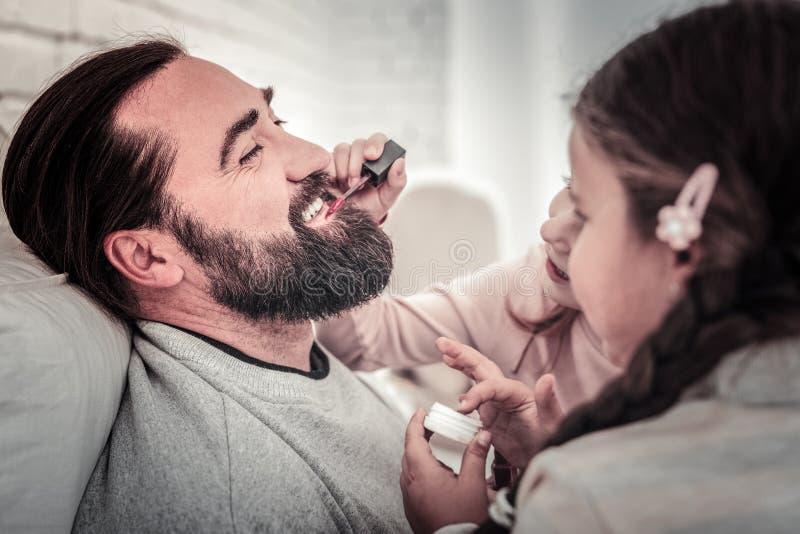 Chiuda su del fronte dei padri che ottiene il suo fronte dipinto dalle sue ragazze fotografie stock