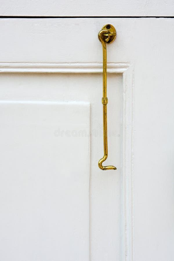 Chiuda su del gancio d'annata della finestra di colore dell'oro o del gancio d'ottone dell'otturatore che appende sul fondo di le immagine stock libera da diritti