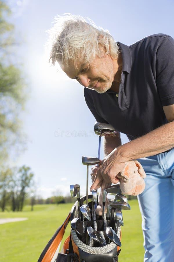 Chiuda su del giocatore di golf maschio che prende il club di golf immagini stock libere da diritti