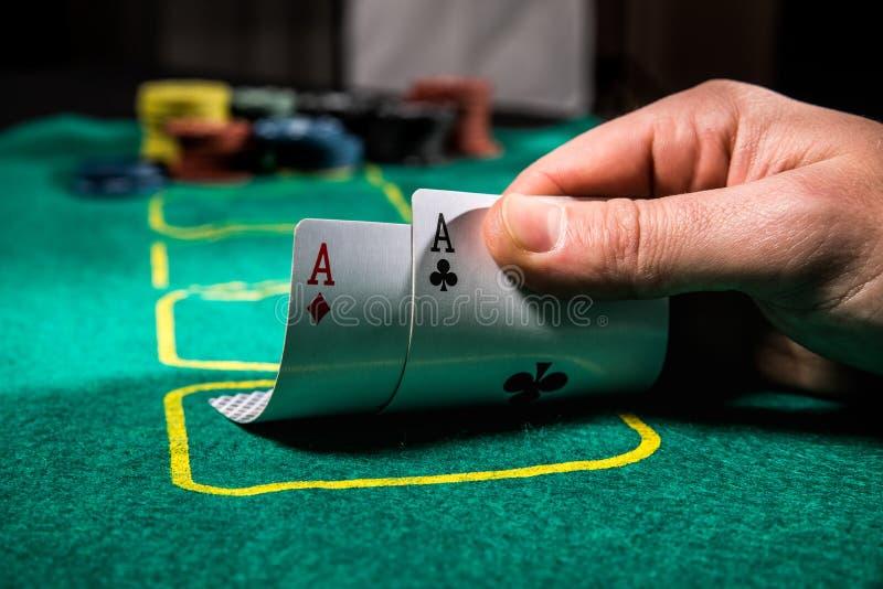 Chiuda su del giocatore di poker con due carte da gioco e chip degli assi alla tavola verde del casinò immagini stock libere da diritti