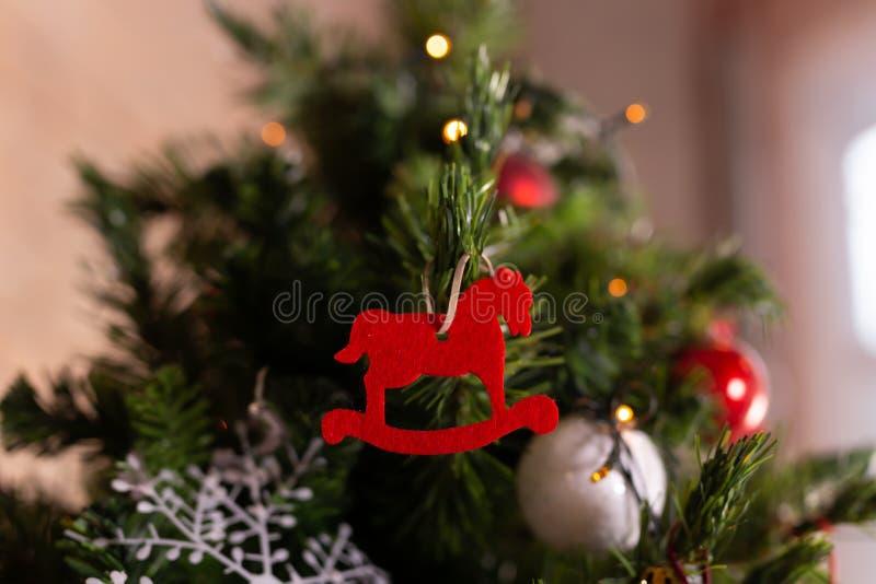 Chiuda su del giocattolo rosso del cavallo di natale sull'albero di Natale Concetto di Natale e del buon anno immagine stock