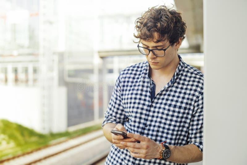 Chiuda su del giovane che esamina lo schermo del telefono cellulare la stazione della metropolitana fotografia stock