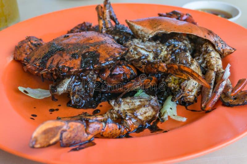 Chiuda su del granchio del pepe nero servito sul piatto arancio luminoso fotografia stock libera da diritti