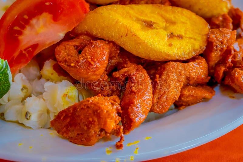Chiuda su del hornado delizioso, alimento andino tipico tradizionale ecuadoriano servito con cereale, la patata, plantano dolce fotografia stock libera da diritti