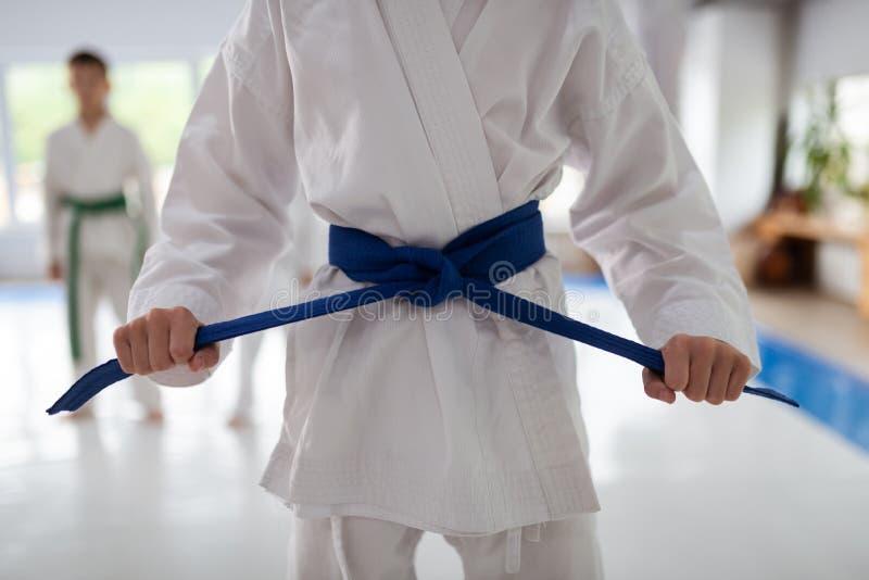Chiuda su del kimono bianco d'uso della ragazza che lega la sua cinghia blu immagini stock libere da diritti