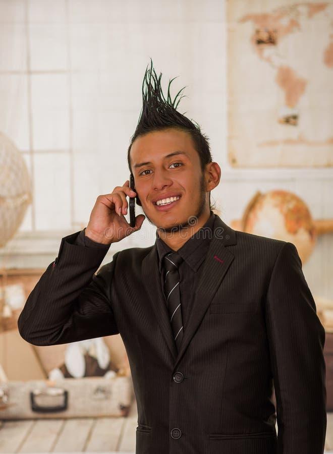 Chiuda su del lavoratore punk dell'ufficio felice che indossa un vestito con una cresta, facendo uso del suo cellulare nell'uffic fotografie stock