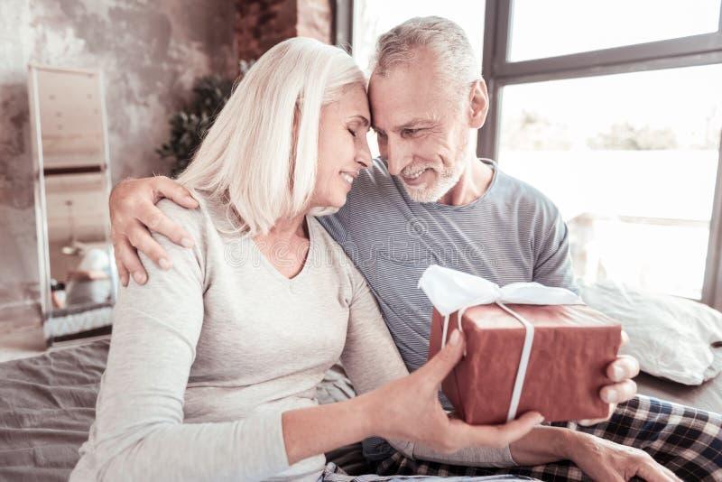 Chiuda su del marito positivo che fa un presente per la sua moglie immagini stock libere da diritti