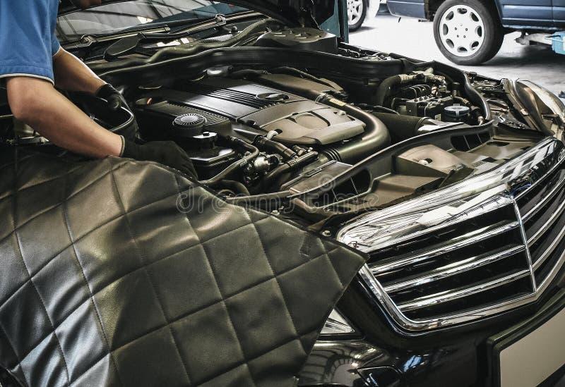 Chiuda su del meccanico maschio che lavora al motore nella riparazione automatica fotografia stock