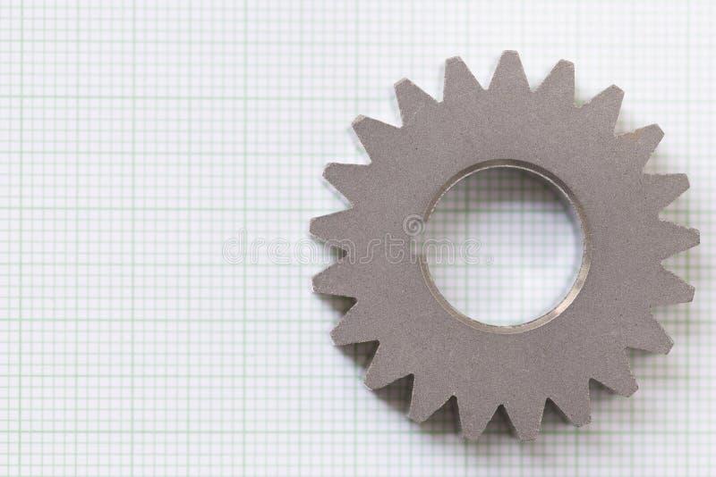 Chiuda su del metallo dell'ingranaggio su carta millimetrata immagine stock