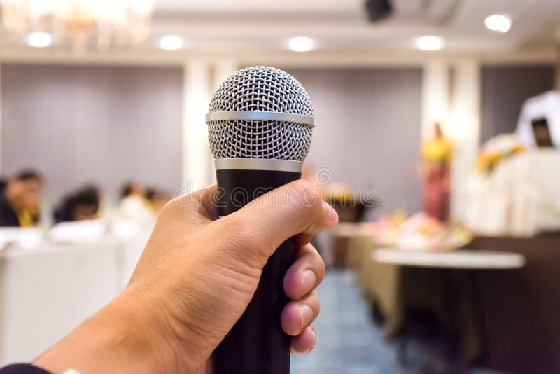 Chiuda su del microfono della tenuta della mano del ` s dell'uomo nella sala per conferenze fotografie stock libere da diritti
