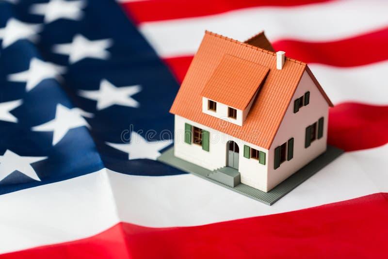 Chiuda su del modello della casa sulla bandiera americana fotografia stock libera da diritti