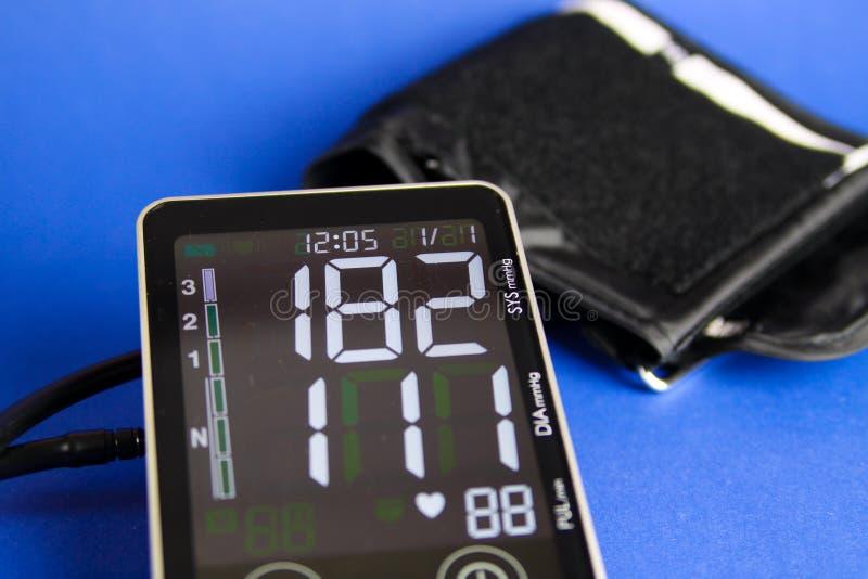 Chiuda su del monitor digitale dello sfigmomanometro con il polsino che mostra l'alta pressione sanguigna diastolica e sistolica immagine stock