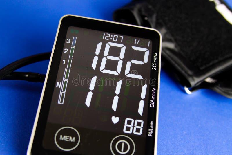Chiuda su del monitor digitale dello sfigmomanometro con il polsino che mostra l'alta pressione sanguigna diastolica e sistolica immagini stock