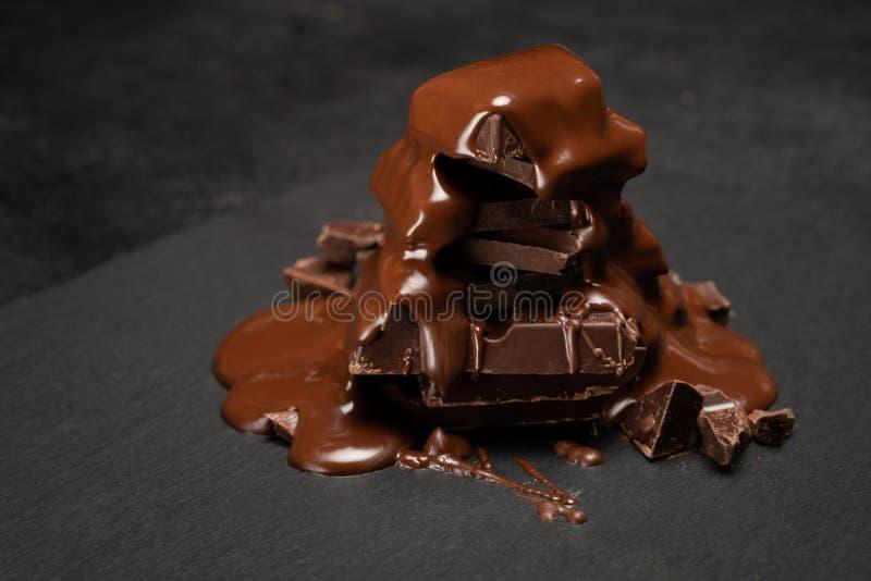 Chiuda su del mucchio dei pezzi del cioccolato o mucchio e sciroppo di cioccolato fuso su fondo concreto scuro immagini stock