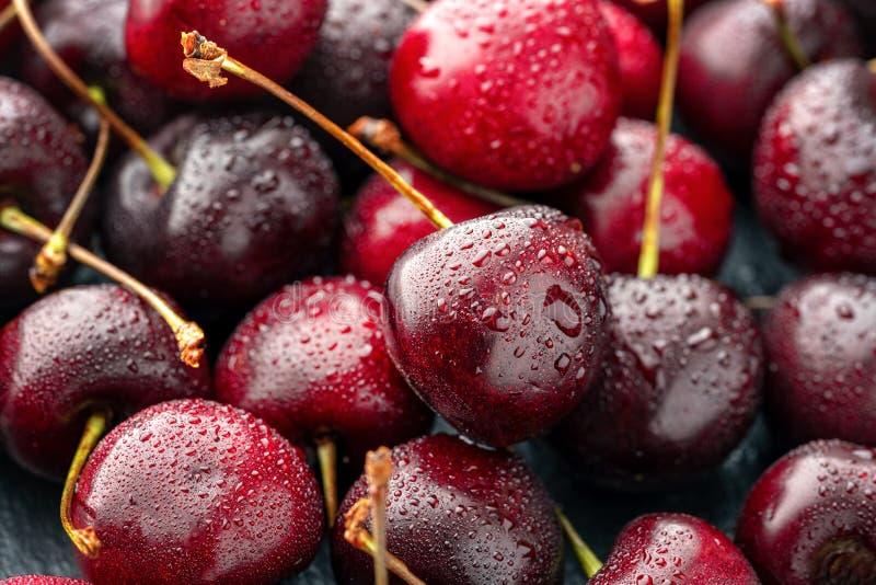 Chiuda su del mucchio delle ciliege mature con i gambi Ampia raccolta delle ciliege rosse fresche Priorit? bassa matura delle cil fotografia stock