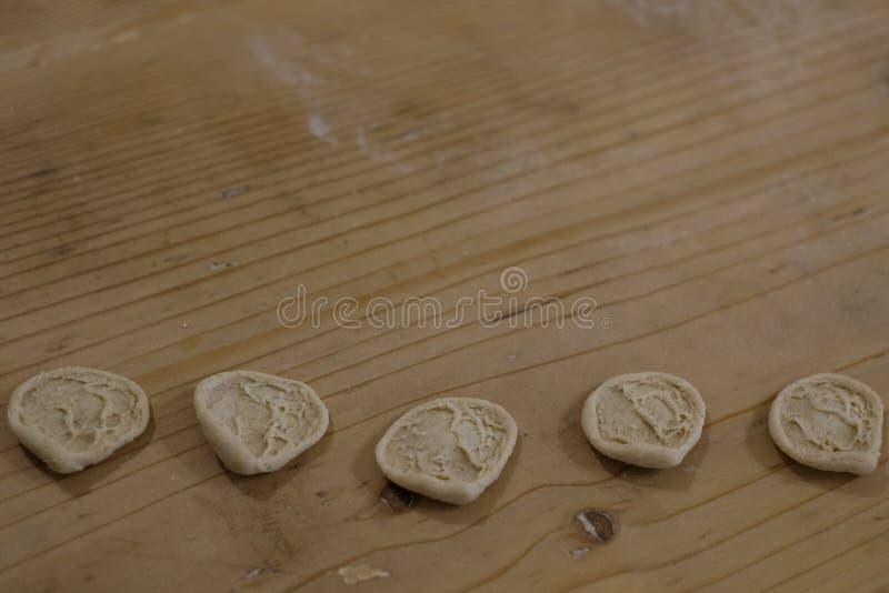 Chiuda su del orecchiette appena fatto, pasta auriforme su una tavola di legno, tradizionale alla regione della Puglia di Italia immagine stock